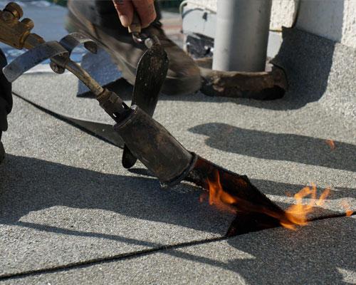 Dakdekker voert dakreparatie uit Bitumen dakbedekking laten branden